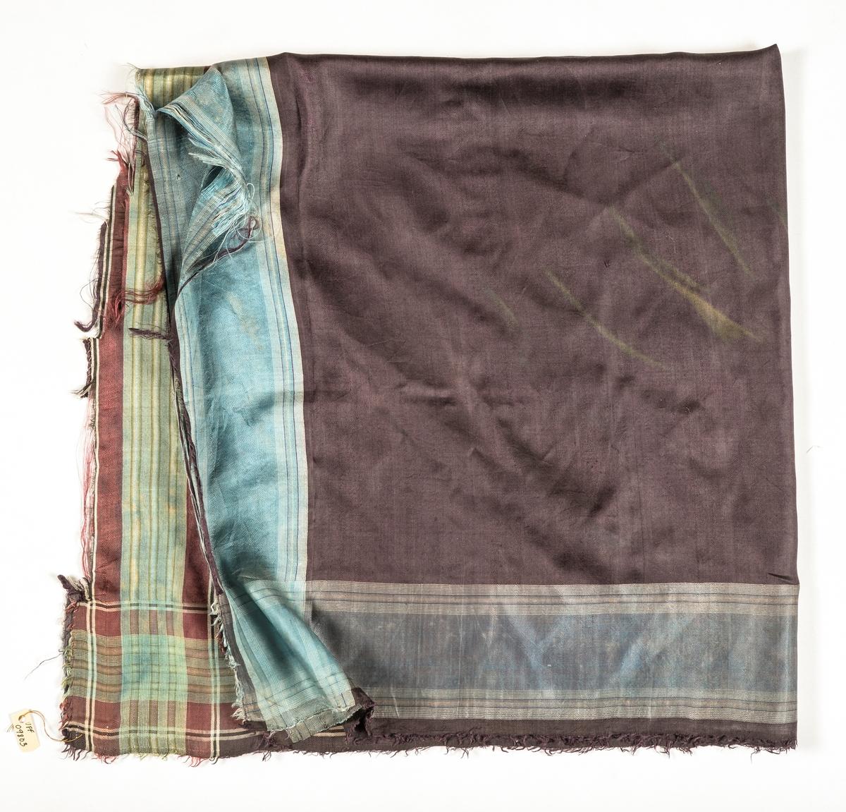 Tørkle i svart kypertvove silke. Bordar langs kantane i blått, kvitt og svart på to sider, og fiolett, grønt og svart på dei to andre. To-preikeplagg. Frynser rundt kantane.