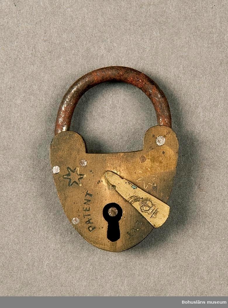 """Nyckel saknas. På framsidan instämplat: """"Patent"""" på två ställen samt en sexuddig stjärna. På nyckelhålsskyddet stämplat: """"En krona"""" och därunder """"VF""""."""