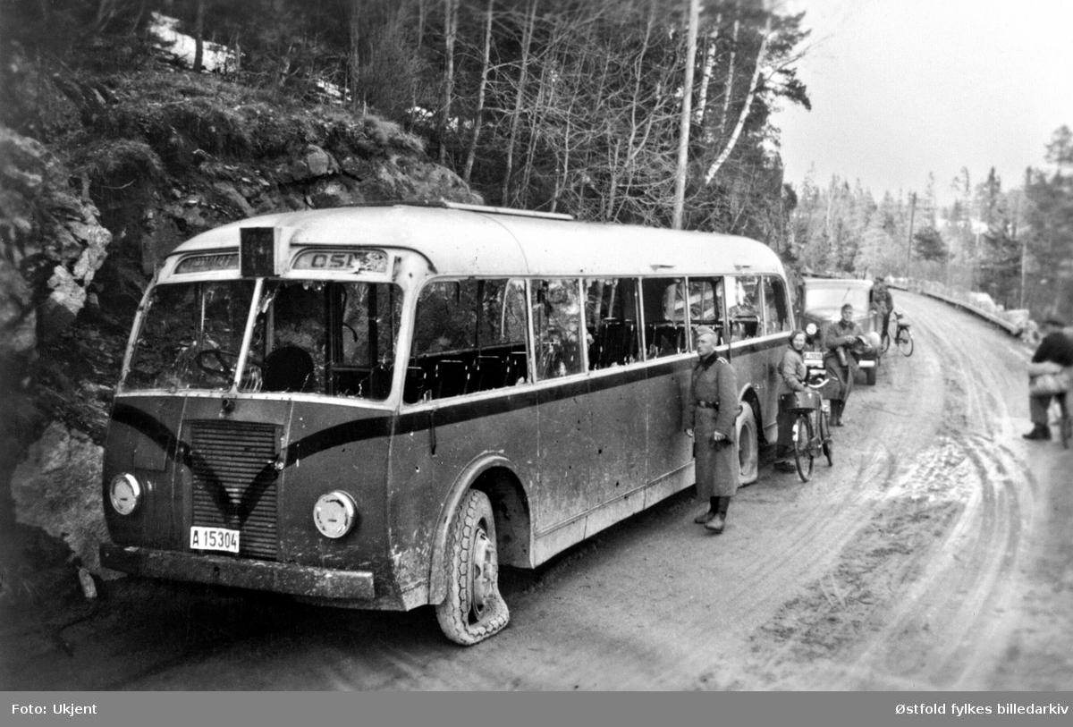 Sønderskutt buss ved Fossum bru, Spydeberg. Tysk soldattransport. Bussens registreringsnummer: A-15304.  Bussen transporterte tyske soldater fra Oslo til Fossum i Spydeberg i april 1940. Ble kjørt av norsk, sivil sjåfør. Norske styrker lå i dekning på østsiden av brua og tok bussen under ild med maskingevær like før den skulle svinge inn på brua. Mange tyskere ble drept. Sjåføren ble skadet men overlevde.