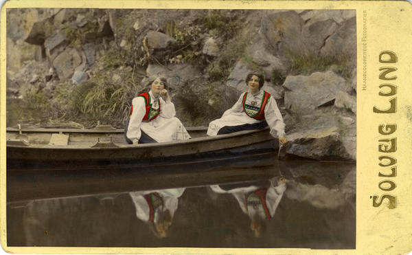 Kolorert fotografi av to kvinner med drakt i pram. 1908.. Foto/Photo
