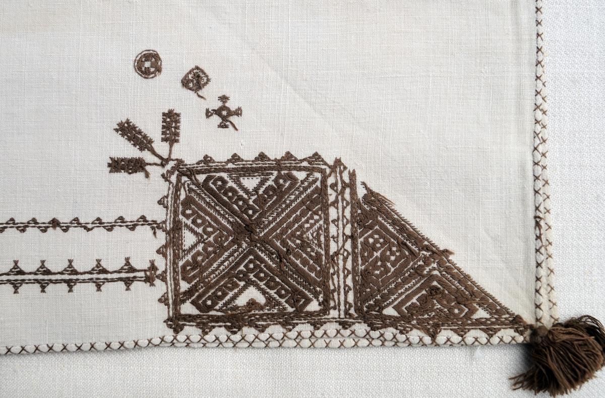 Geometriskt mönster i kvadrater i hörnen, bårder mellan kvadraterna på ryggsnibb och framsnibbarna.  På ryggsnibben tre kvadrater och en majstångsspira utan spira samt märkning med årtal och initialer.  På varje framsnibb en kadrat och en trekant.  Ornament: Figurer i korsstygn och rätlinjig plattsöm