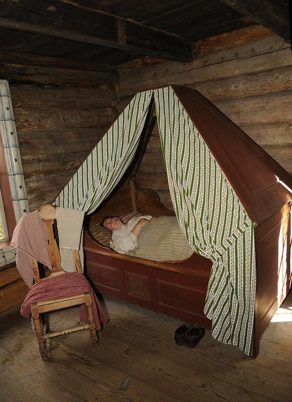 Jente ligger i himmelseng og sover med hendene pent oppå dyna. Skoene står under senga, og klærne henger på en stol ved siden av senga. (Foto/Photo)