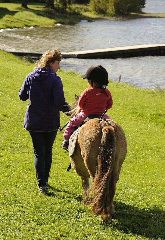 Barn med hjelm rir på en liten, brun ponny. Voksen dame går ved siden av og leier hesten. (Foto/Photo)