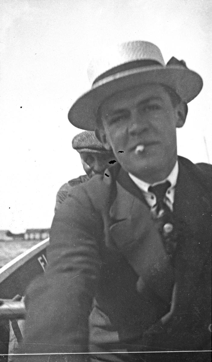 På rotur. To menn som ror, den nærmeste røyker. Sjøhus i bakgrunnen. Hverdagsfoto.