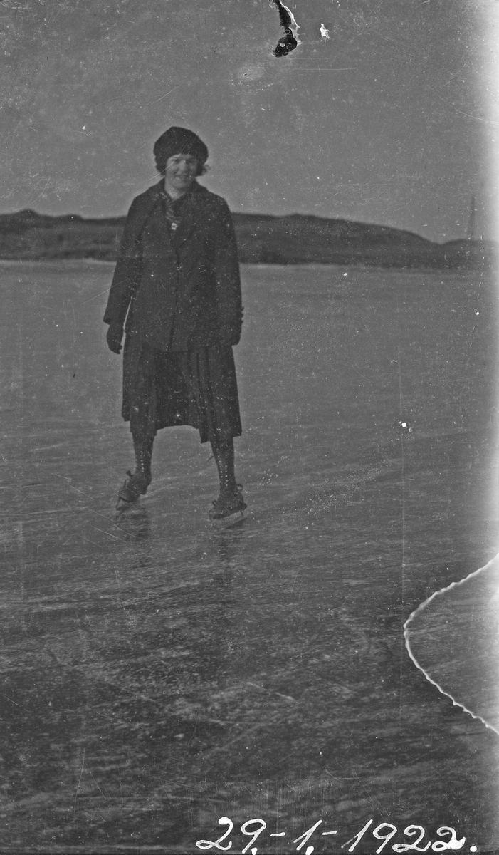 Vinter. En kvinne på skøyter poserer på isen. Hverdagsfoto.