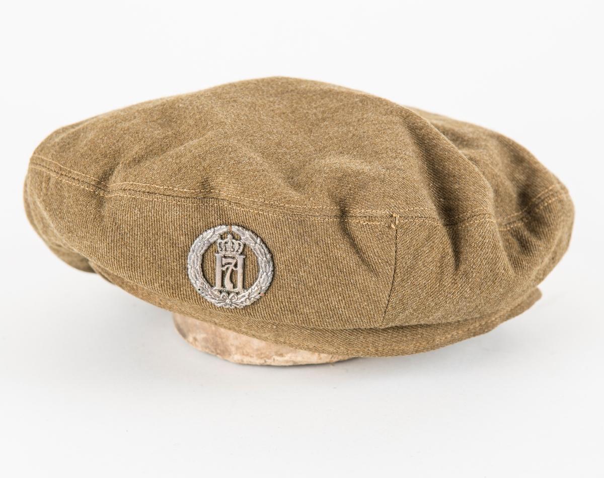 """Militærlue, """"Beret"""" i brun-grønt ulltøy. Rundt tinnmerke påsydd framme med motiv Håkon 7.."""