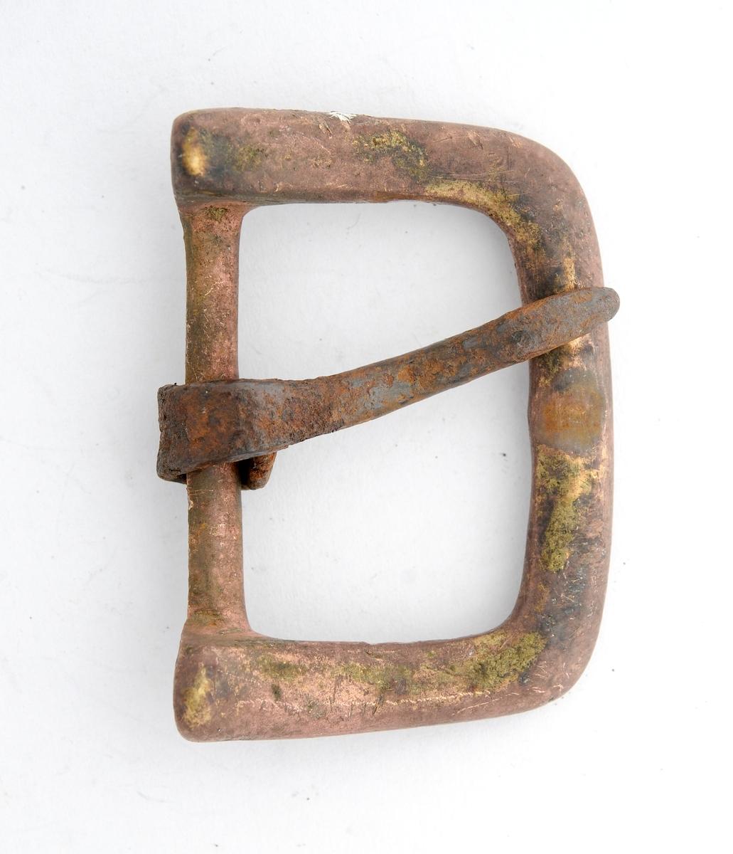 Beltespenne i messing. Rektanguler form. Ingen dekor. Stolpen er støypt i eitt med spenna, tann i jern smidd rundt.