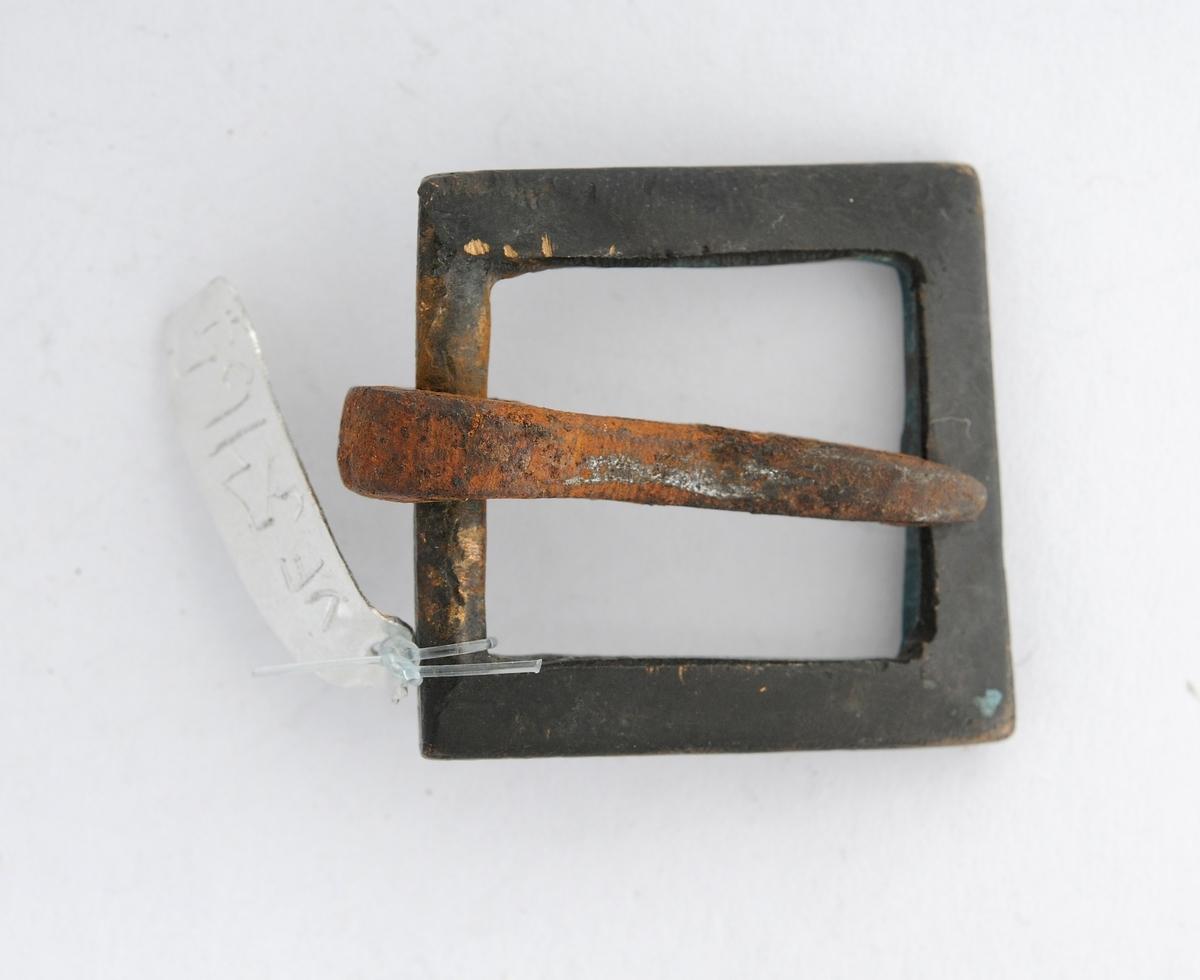 Spenne støypt i bronse. Kvadratisk form. Tann i jern er smidd rundt eine enden.