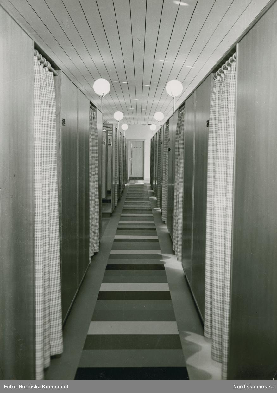 """Interiör. Lång korridor med tvärrandig matta. Längs båda sidor bås med rutiga förhängen. Nordiska Kompaniet. Text med blyerts på baksidan: """"Hygieniska avdelningen""""."""