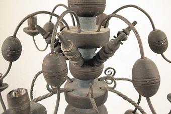 Svartmålad ljuskrona av trä med 12 ljusarmar av järn. Ljushållare av trä. Enligt uppgift i arkivet har kronan följt med Härjevadskyrkan till Fornbyn i Skara.  Kronan togs in till samlingarna 2002 och ersattes med nytillverkad.