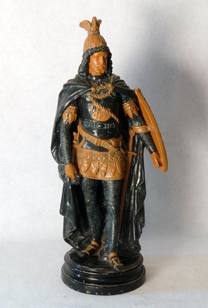 """Statyett föreställande Lohengrin i full krigardräkt med slängkappa och sköld. Målad i grönt, svart och gult och stående på svartmålad sockel på vilken namnet """"Lohengrin"""" står skrivet. Se även 73074"""