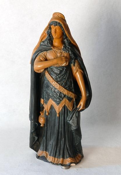 """Statyett föreställande """"Elsa ur Wagners opera Lohengrin. Lång draperad klänning, slängkappa och huvudbonad, målad i grönt, svart och gult. Se även nr 73073."""