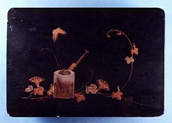 """svart skrin i lackteknik, dekro av blommor, fjäril samt behållare på locket, lacket något nött här och var samt guldpudrat invändigt, inköpt på auktion anordnad av landshövding Ekman för 3,25 kr Text i liggaren:"""" ... å locket konvalvolusranka ...""""   Neg.nr: 1986-0010 Sakord: SKRIN Tillverkningstid: 1800 - 1900 Material: trä lack vitmetall Teknik: lackat målat tappat spikat Mått: L=249 B=175 H=145 Vikt:"""