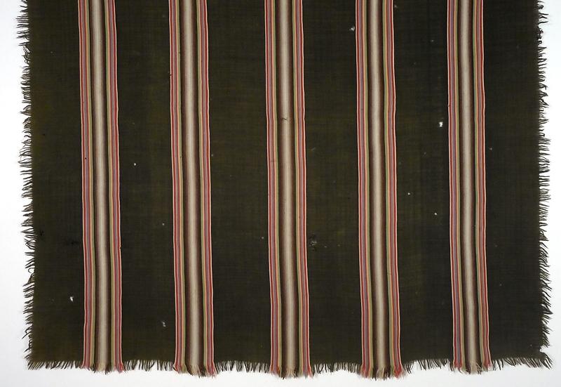 """Enl. liggare: """"Schal, svart med ränder i ett flertal färger av ylle. St. 150 x 145 cm  1887  tillhört hennes (givarens) morfar och mormor, """"fästmögåva"""", se brev"""