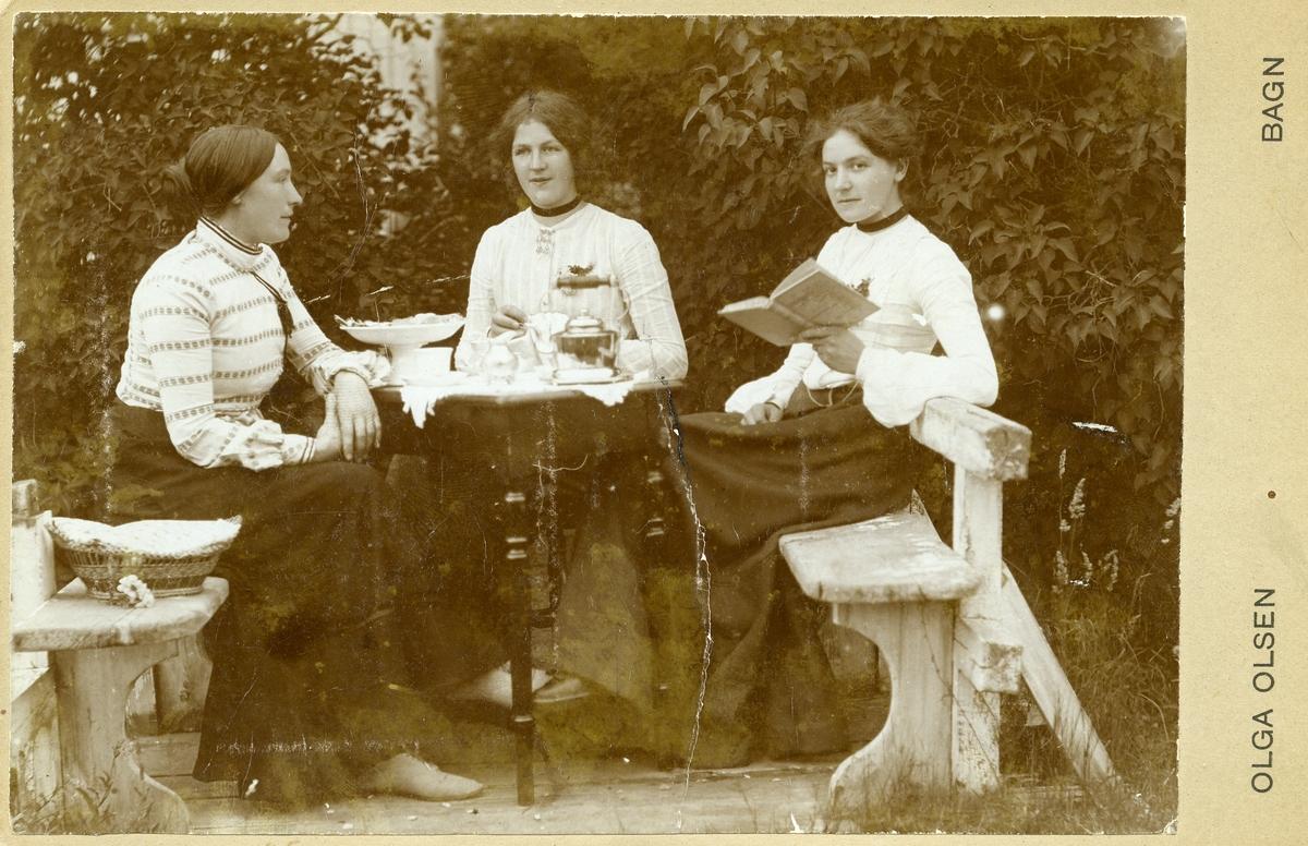 Tre kvinner sit rundt eit bord i ein hage.