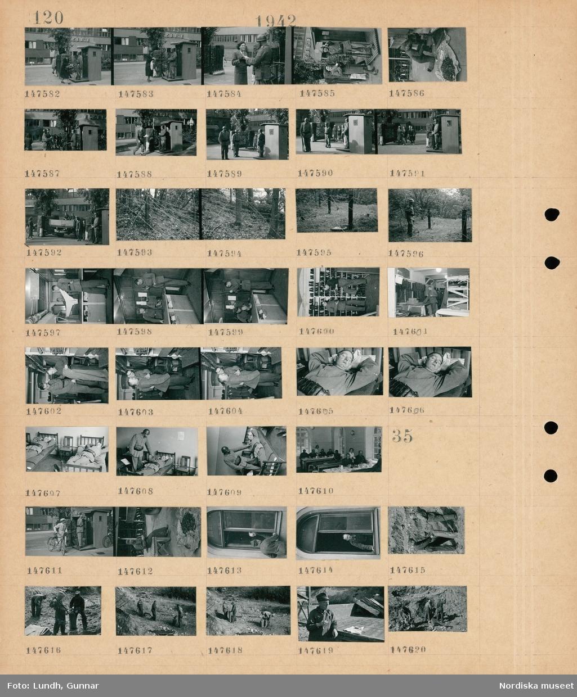 """Motiv: (ingen anteckning) ; En kvinna visar ett papper för en soldat som står vakt i en vaktkur vid en byggnad med skylt """"Esselte"""", en soldat arbetar med ett gengasaggregat på en lastbil, taggtråd i skogen, en soldat vid ett taggtrådshinder, interiör med soldater som står vid en tvättinlämning, två soldater står vid hyllor med skor, en man provar en uniform, en soldat sover i en säng,interiör med soldater som sitter vid ett bord och äter och blir serverade av kvinnor.  Motiv: (ingen anteckning) ; En man med cykel samtalar med en soldat som står vakt vid en vaktkur, en soldat i ett öppet fönster, soldater fyller sandsäckar."""