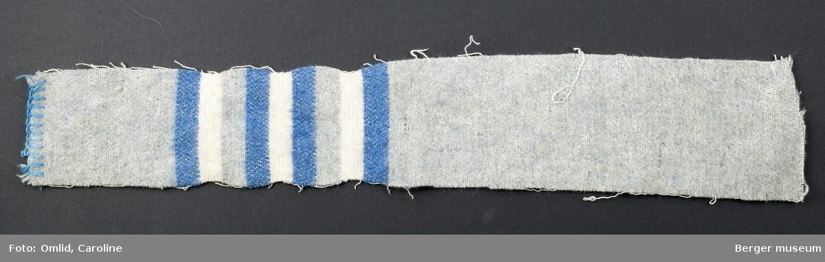 En prøve. En blå prøve er klippet av. Ensfarget gråblå med striper i mørk blå og hvit.