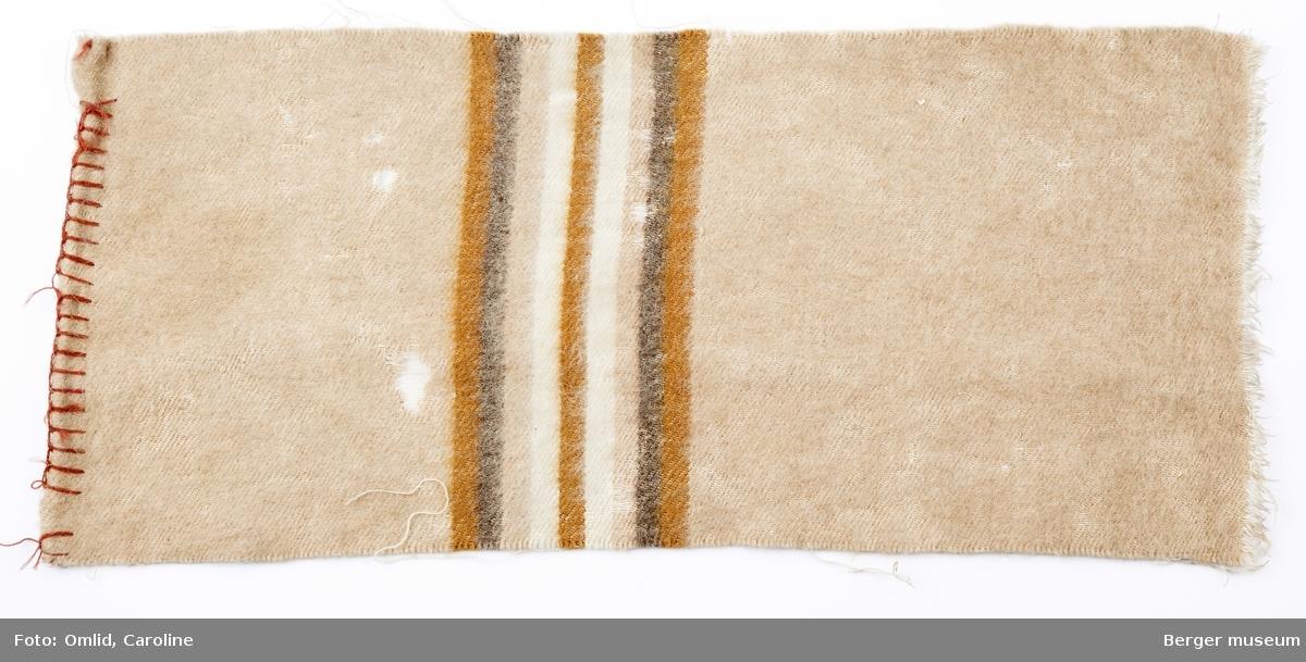 Ensfarget teppeprøve i mørk beige. En bord i striper på tvers.