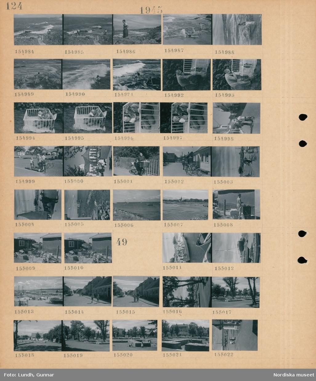 Motiv: (ingen anteckning) ; Människor badar på en badstrand, en man vid ett barn i en spjälsäng, stadsvy med fotgängare och cyklister, en hamn med båtar, segelbåtar på havet, fiskebodar med fiske tinor på marken.  Motiv: (ingen anteckning) ; Människor på kajen vid en båt, en hamn med båtar, stadsvy med fotgängare - cyklister och en buss med gengasaggregat, vy över en park, barn i en park.