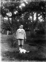 Pojke och katt i trädgård, Skinnarbo, Simtuna socken, Upplan