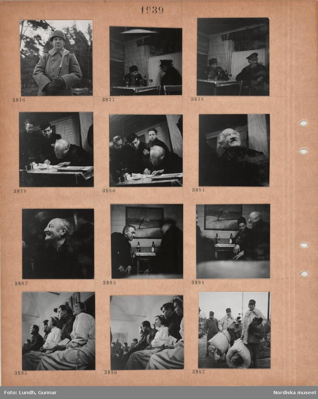 Motiv: Man i uniformsrock och hjälm håller ett gevär med bajonett, två män sitter vid ett bord och dricker öl, kvinnor i vita särkar och glitter i håret sitter i bänkar bredvid män i militära kläder, två män i militärpäls håller i varsin hoprullad madrass.