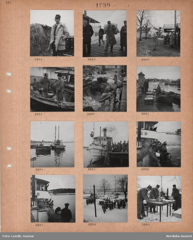 Motiv: En man i militärpäls och skärmmössa står vid en höbale, män i militära kläder på en brygga vid en skärgårdsbåt, män bär hoprullade madrasser, fiskebåt vid brygga, två fiskare väger upp strömming, strömmingslådor på brygga, i bakgrunden en skärgårdsbåt, mindre fartyg vid skärgårdsbrygga, män i militärrockar på brygga, skärgårdsbåten Gustavsberg III med militärer som passagerare, militär matlagning utomhus.