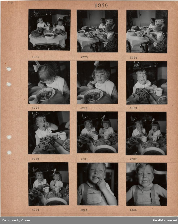 Motiv: Liten pojke och flicka sitter och äter vid ett lågt fullt dukat bord.