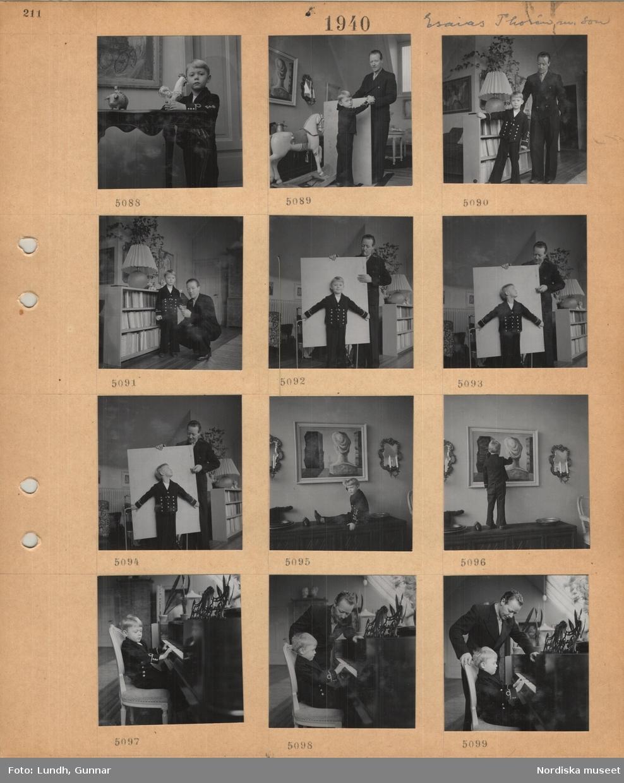 Motiv: Konstnären Esaias Thorén med son, liten pojke håller i en tuppfigur, far och son vid gunghäst, vid låg bokhylla, pojke sitter på ett lågt skåp, tavla och ljuslampetter på väggen, pojke står på skåp och pekar på tavla, pojke sitter vid piano, pappan står bredvid.