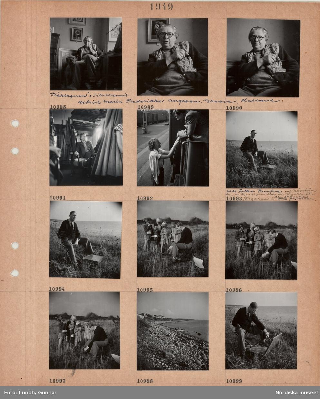 """Motiv: En kvinna, """"Plåtslagaren"""" = silversmed Astrid Marie Frederike Aagesen Grevie, Halland, klädd i långbyxor och kofta sitter i en stol med en hund bredvid, en kvinna sitter i en tågkupé, tåg vid perrong, en kvinna och en man tar avsked, en man, konstnären Nils Folke Knafve, sitter på en pall i naturen vid havet med ett målarskrin, visar en grupp barn som har plockat bär hur han målar, stenig strand nedanför villabebyggelse."""