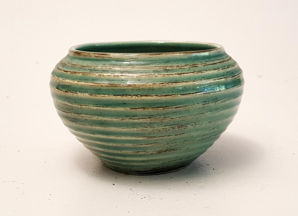 Krukke eller bolle i keramikk. Grøn glasur. Riller på utsida. Smalnar inn mot opninga oppe.