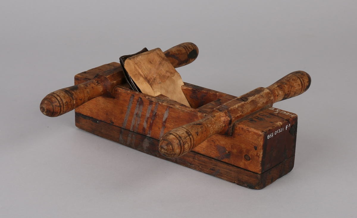 Okshøvel. Firkantet trehøvel med skjær av jern som kan reguleres. Påmontert to doble håndtak.