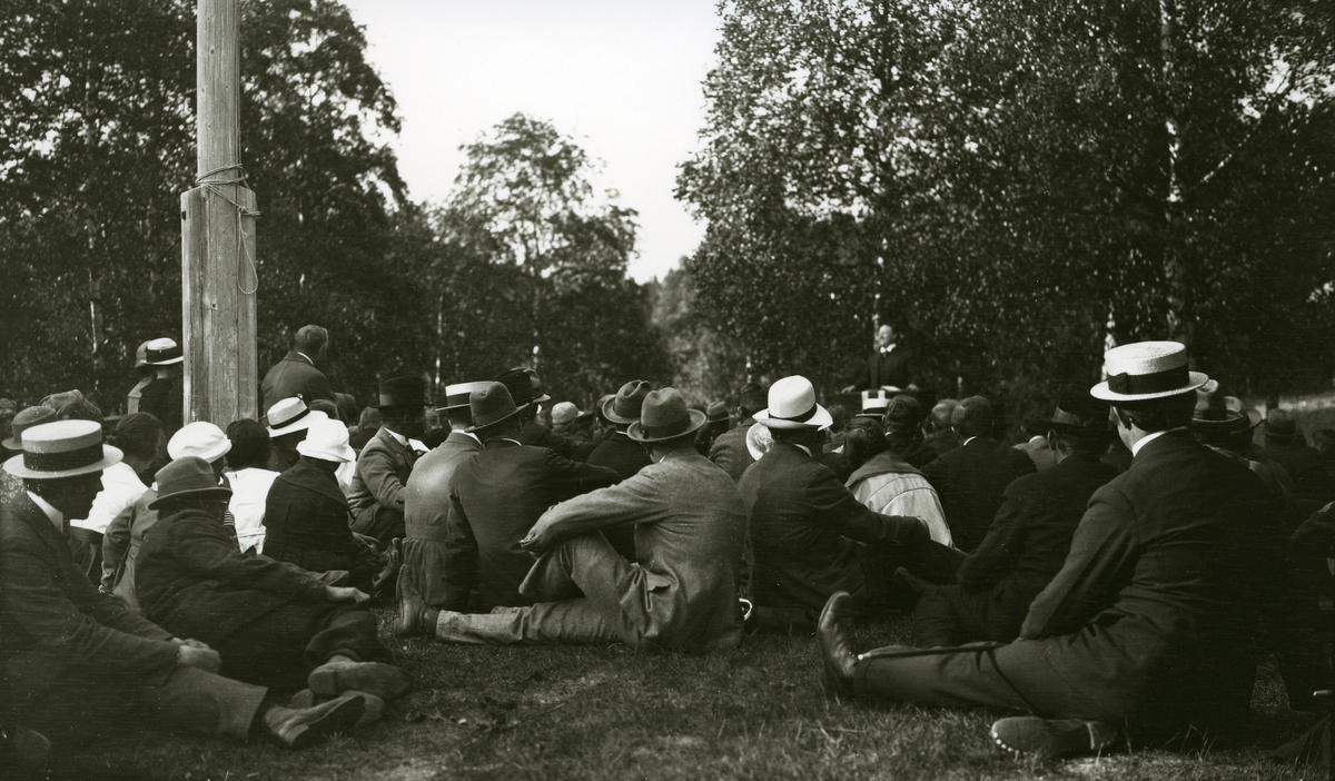Masse mennesker forsamlet (sittende) foran taleren; Edvard Drabløs (1883 - 1976). I Innbygda.