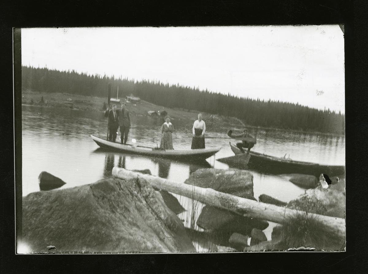To kvinner og to menn står i en robåt på Høleravatnet. Solvangen i bakgrunnen.