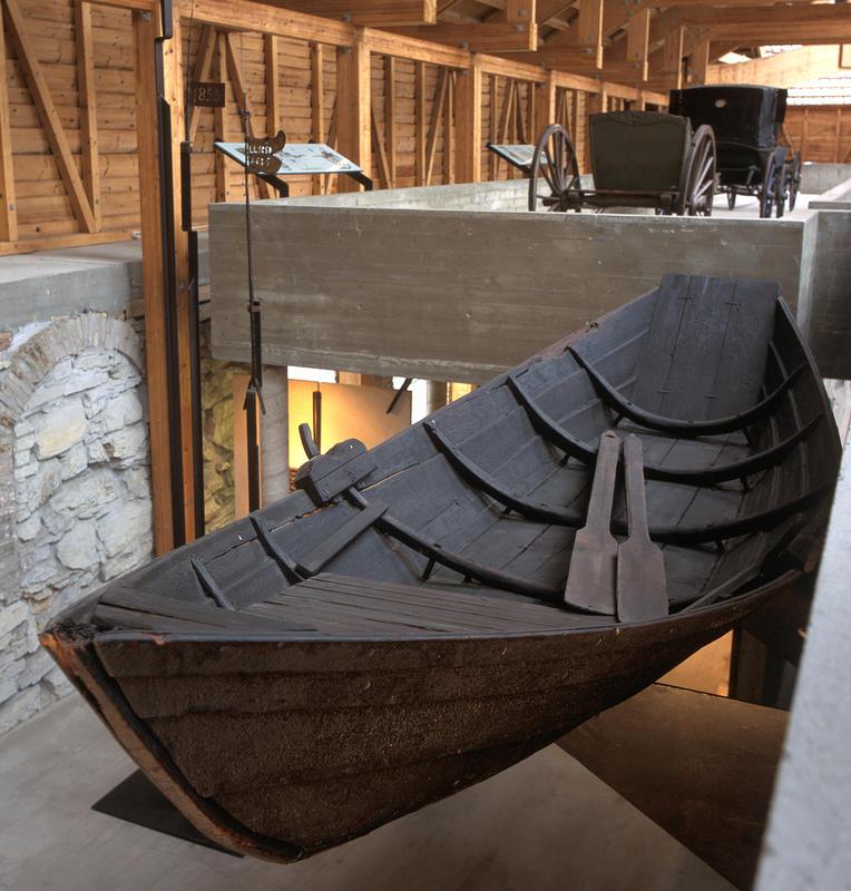 Mørkebrun robåt i tre henger oppe i utstilling i Storhamalåven, et par årer hviler i bunnen av båten.