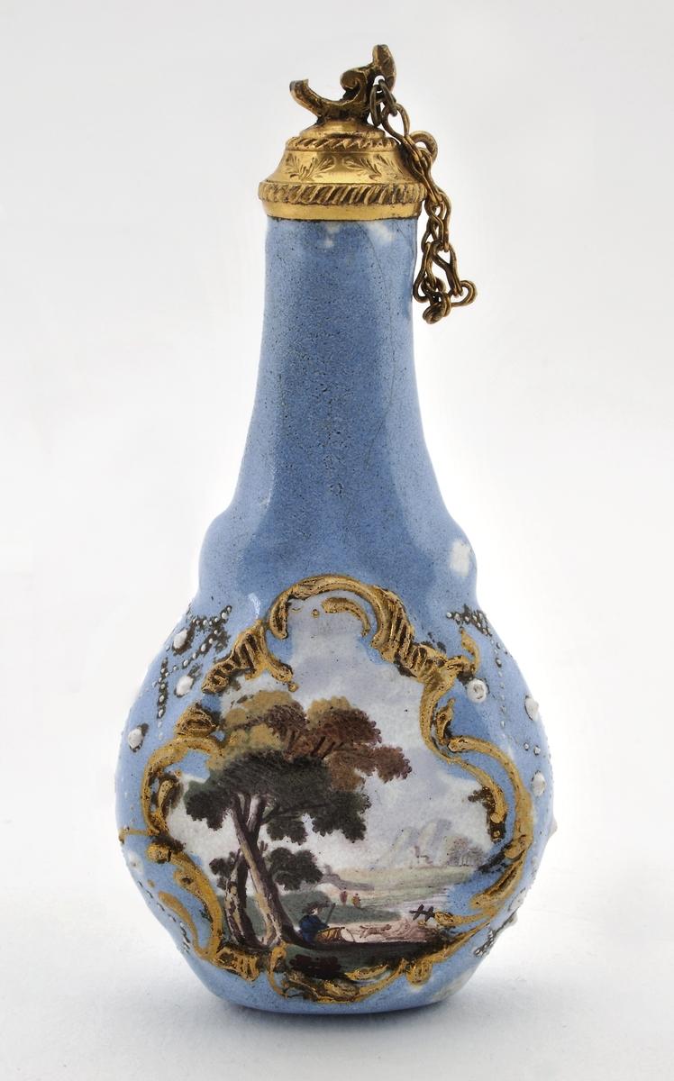 Parfymflaska, fajans, med propp av gul metall, ljusblå med landskap i rokokokartuscher.