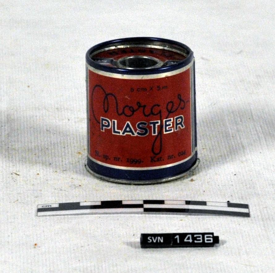 Sylindrisk metallboks. Boksen er blå, med ramme i sølv og rød innenfor rammen. Boksen består av to deler, en holder og et omslag.  Holderen har hull i gjennom i høyderettning.