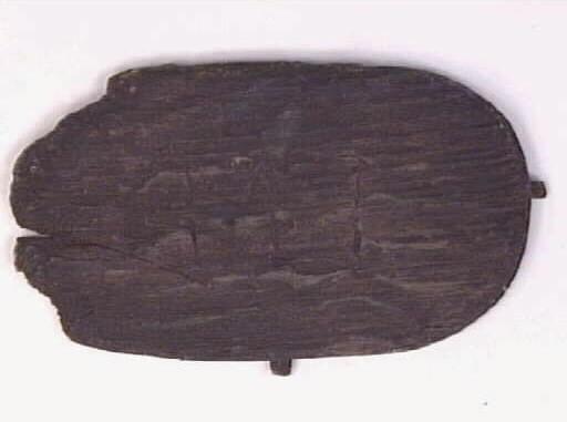 En oval botten till en svepask. Bottnen har något avfasade kanter samt två kvarsittande träpligg. Bottnen är sliten, spruken samt avnött längs kanterna. På botten finns ett inristat bomärke/initialer; MI.