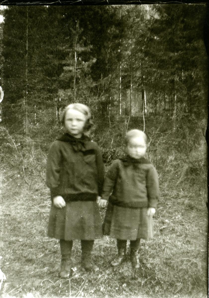 To barn står ute i skogen.