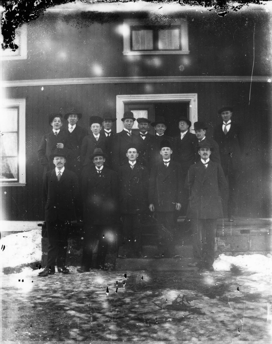 Grupp om femton män samlade vid farstubro.