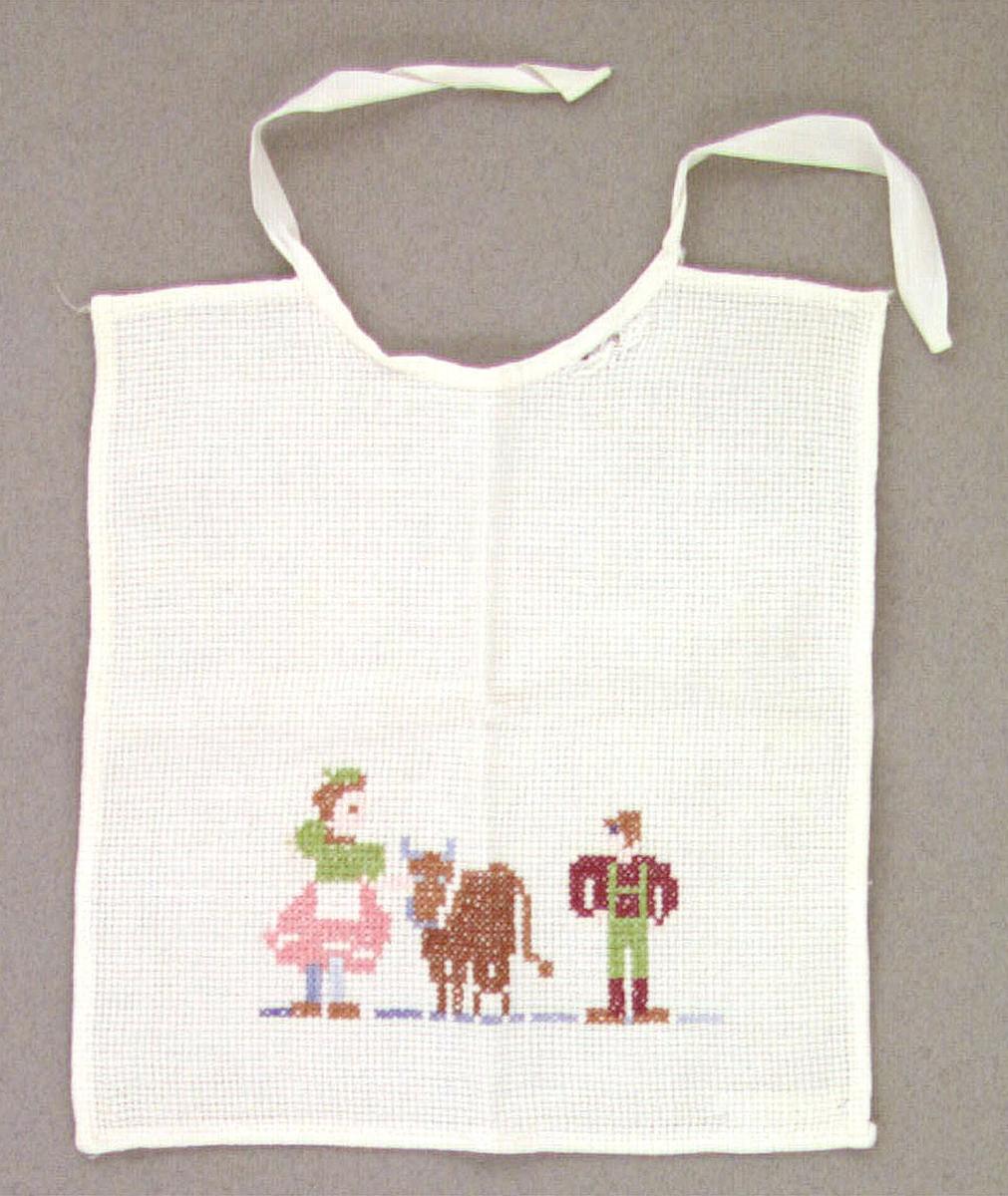 Dockhaklapp av vit bomullsstramalj med korsstyngsbroderi föreställande en gammal gubbe och en ko. Knytes med ett bomullsband i halsen.