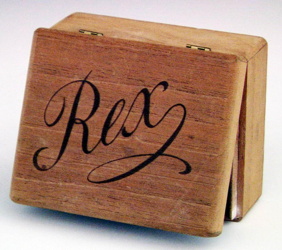 Ask av trä märkt med lock försett med två gångjärn av mässing. Rex som text på locket. Har använts som nipperask.