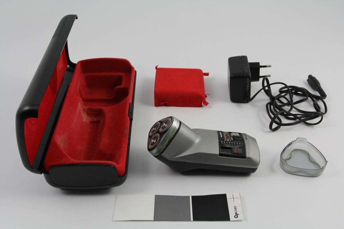"""Barbermaskin i etui: a) Barbermaskinen er formet som en avrundet sylinder med trekantformet hode. Skal være lett å holde i hånden. 3 sirkulære skjærere i front. Betjenings panel. I front sitter et løst deksel, plast, transparent. Avrundet trekant L-5,5cm B ca.5.  c) Ledning m/kontakt og adapter L 158cm adapt. LxBxH:6x5x3 cm d) Løst """"lokk"""" innvendig for oppbevaring av ledning. e) Etui avlangt, avrundet med formtilpasset innside dekket med rød velur."""
