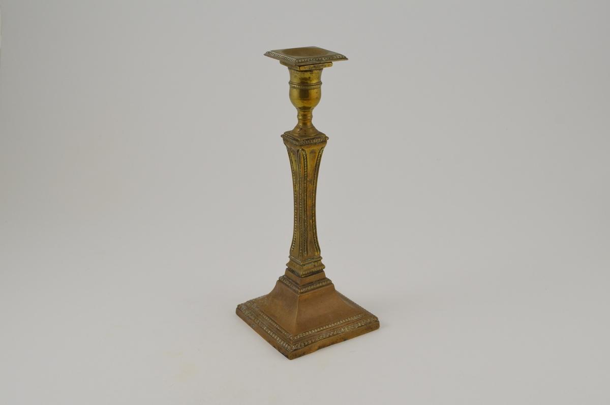 Firkantet fot og midstykke, sylinderformet toppdel med firkantet rand.