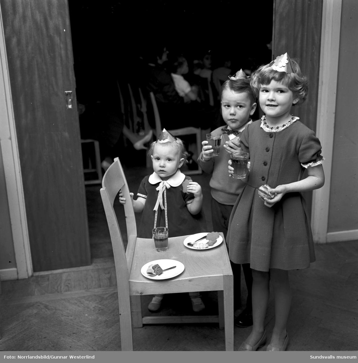 Barn med pappershattar på julfest i Bergsåkers Folkets hus. Arrangör är Bergsåkers kvinnoklubb.