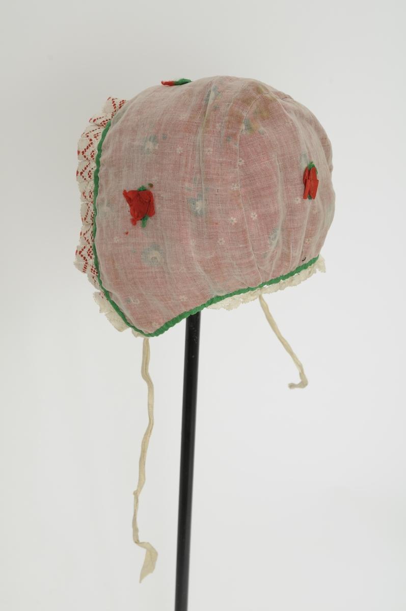 Dåpslue av raudt blomstra bomullstøy med kvitt cambrik over. Kanta med grønn silke. Påsett ein pipefoldakant med blonde og raud silke langst framkanten. Fire små bitar (rosettar) i rosa og grønt. Fòra med ubleikt bomullstøy. To knyteband i kvit bomull.