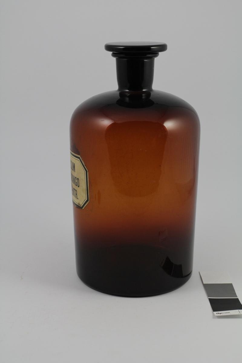 Brunt standglass med smal hals, glasspropp. Hvit etikett med svart skrift. Beholderen ble brukt til oppbevaring av løsninger.
