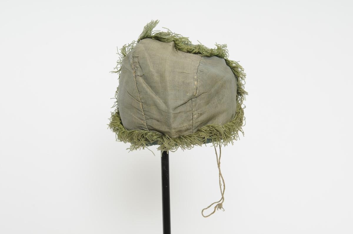 Dåpslue i grønn silke.  Kanting med mørkare grønt ripsband rundt. Gulgrøn frynsekant . Lue i tre deler.  Fòra med lin, grovare på den eine sida.