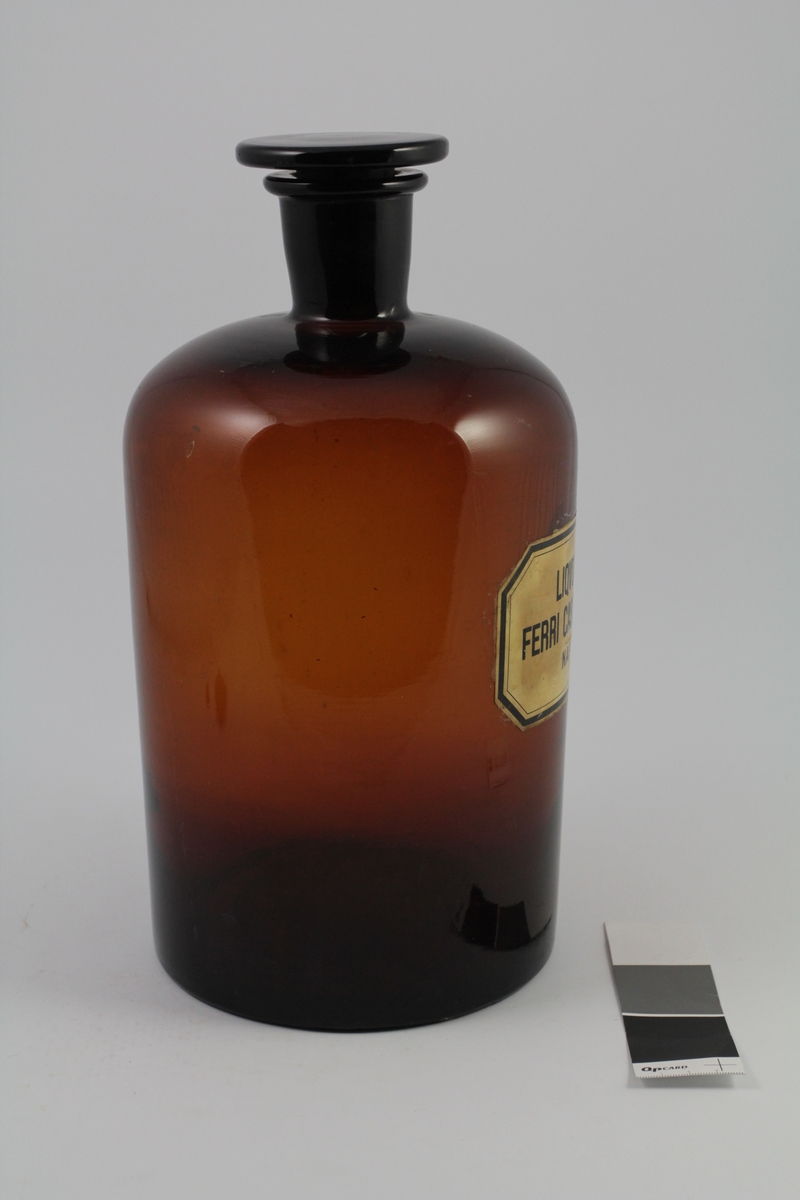 Brunt standglass med smal hals, brun propp. Brukt til oppbevaring av løsninger. Liqvor ferri caseinati NAF ble brukt som jerntilskudd.