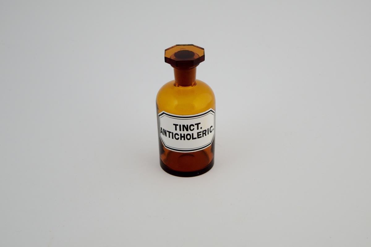Brun glasskrukke med brun glasspropp. Hvit etikett med sort skrift. Tinct. anticholerica ble brukt som et beroligende middel, spesielt på 1800-tallet.