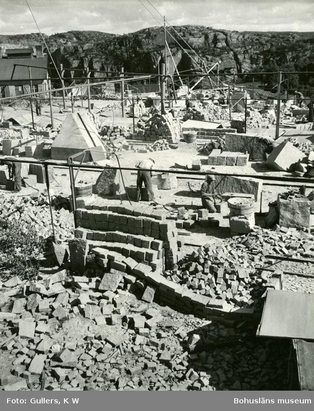 Motiv från stenhuggeri med flera stenhuggare i arbetet samt exempel på olika typer av stenprodukter såsom gatsten, kantsten och större stenblock